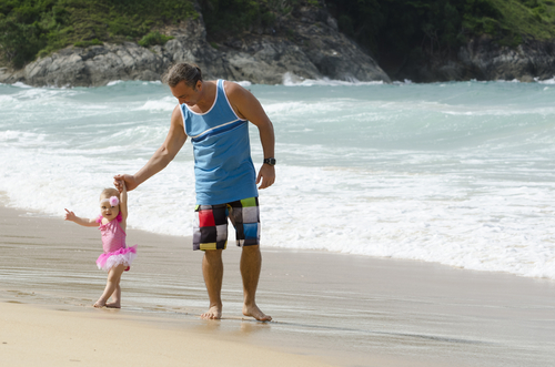 Man holding hand of small child as they walk along a beach