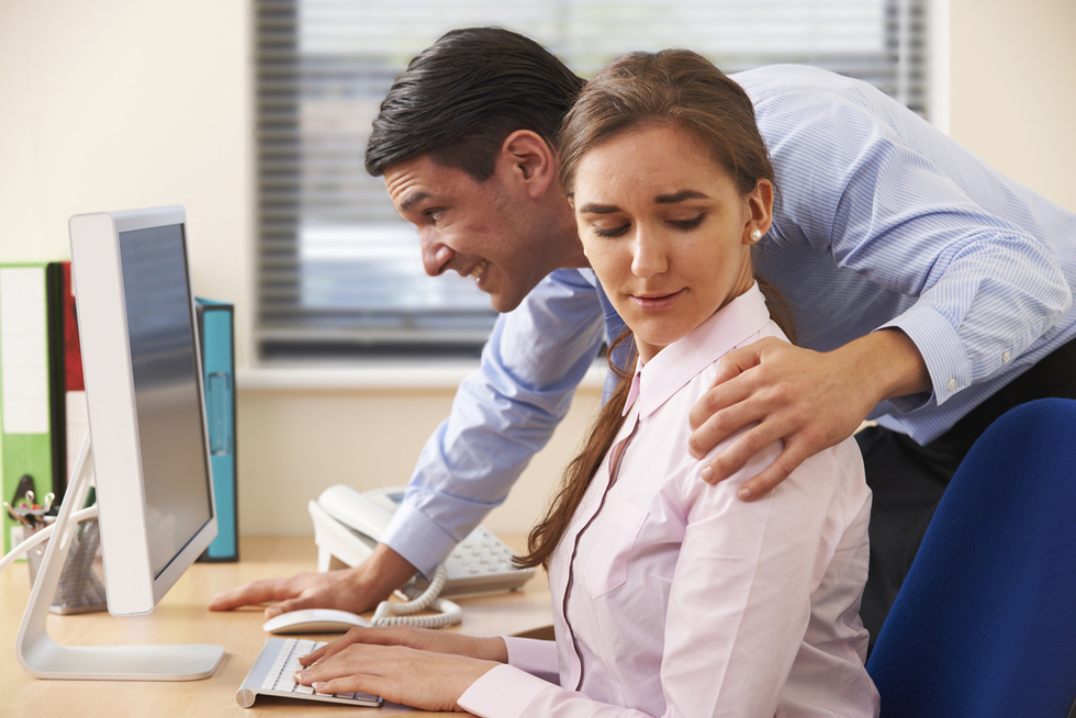 Office-worker-with-hand-on-female-colleague's-shoulder