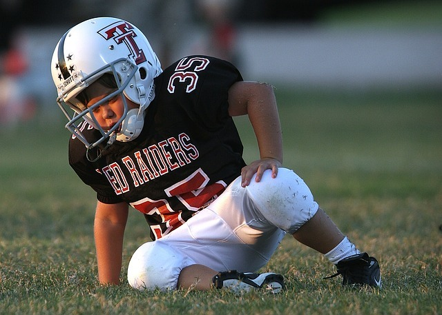 young football player in uniform on ground looking dazed