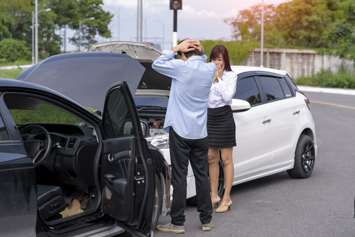 young man and woman looking upset in front of their cars that have just collided