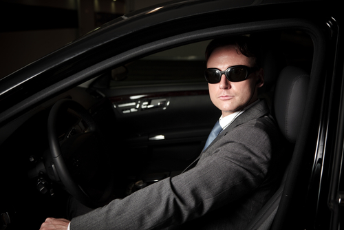driver in sunglasses and suit in dark vehicle
