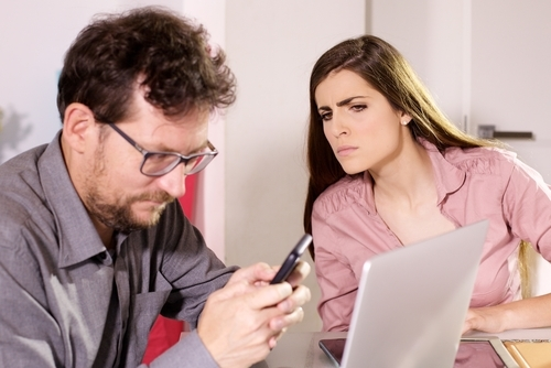 woman looking suspiciously at man who is on phone in front of laptop