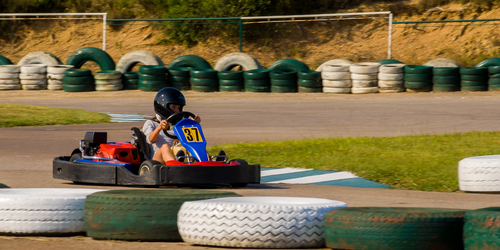 Child in helmet riding a go-kart on on a track lined with tires lying on their sides
