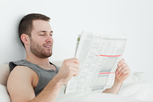 young man reading newspaper in bed