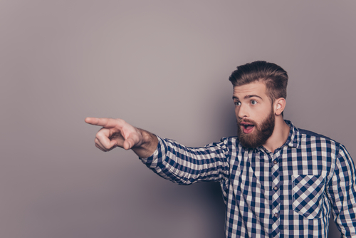 young bearded man pointing finger at something or someone