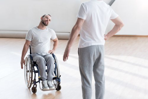 man in wheelchair doing physical therapy with trainer