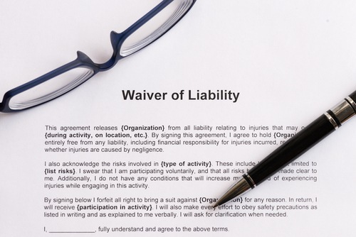 "glasses and pen resting on a document titled ""Waiver of Liability"""