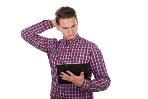 confused young man looking at document on tablet and scratching his head