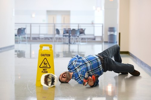 worker in hard hat lying on floor in pain next to wet floor placard
