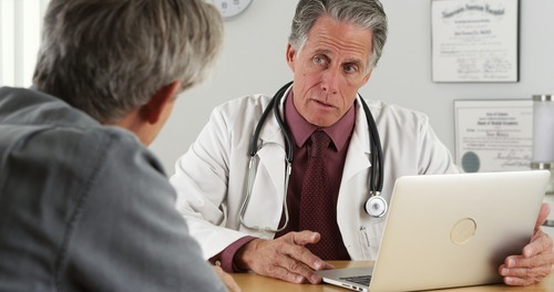 Older male doctor looking at laptop while talking to patient