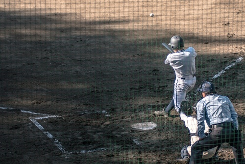 catcher and batter who has just hit ball. Photo from behind home plate net.
