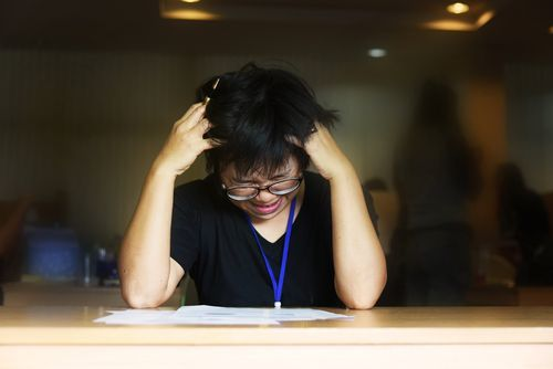 Young Asian woman holding her hands to her head and grimacing as she tries to work on document