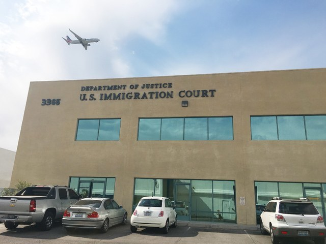 airplane flying over DOJ U.S. Immigration Court building