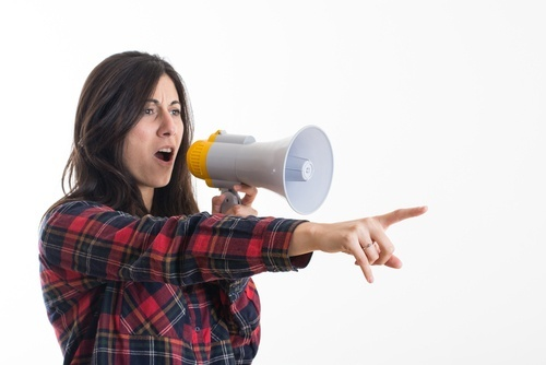 woman shouting into megaphone and pointing finger
