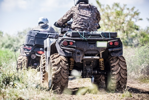 two off road vehicles being driven in the mud by people in camoflage