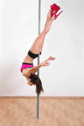 woman hanging upside down on pole in bikini and high heels