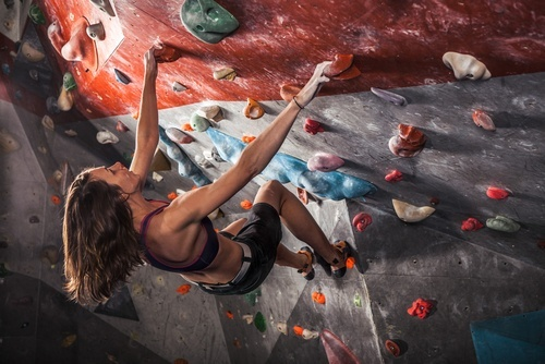 young woman climbing negatively inclined indoor rock climbing wall