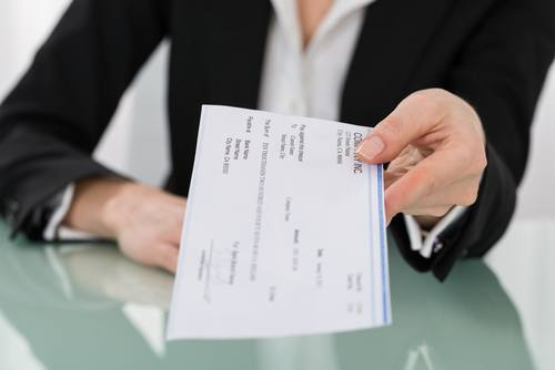 woman in suit holding out a check