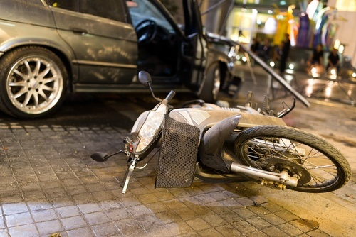 motorcycle on its side after colliding with car