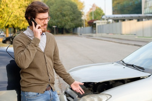 young man making phone call after car accident