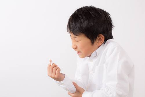 child in white shirt wincing and clutching his lower arm