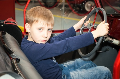 pre-teen child behind wheel of car