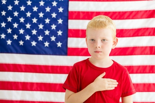 child in front of U.S. flag with hand over heart