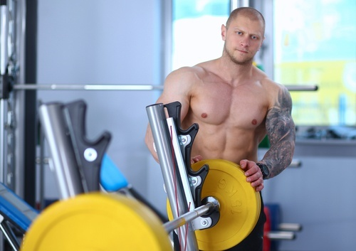 buff shirtless man changing free weights on bench press