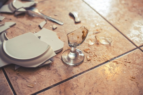 broken plate and glass on a tile floor