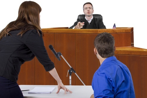 Female lawyer arguing to male judge in chambers with male defendant present at table