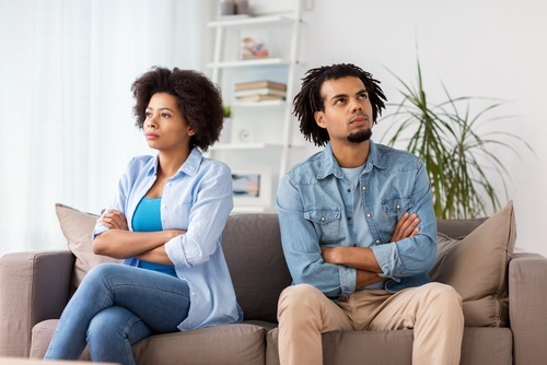 African American couple on sofa not looking at each other