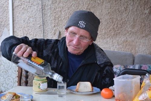 senior man in wooly hat pouring himself a glass of vodka
