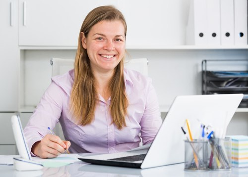 responsible woman sitting behind computer with pen in hand