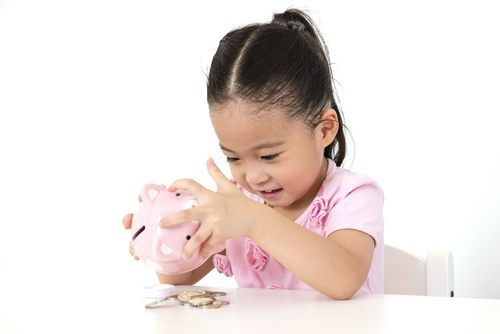 Young Asian girl shaking money out of a piggy bank