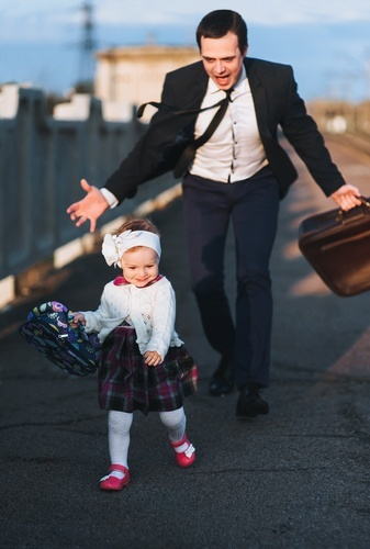 man in suit with large briefcase hurrying a young female child along