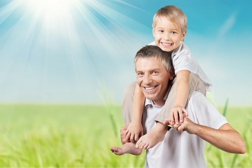 smiling father with young son on his shoulders on a sunny day