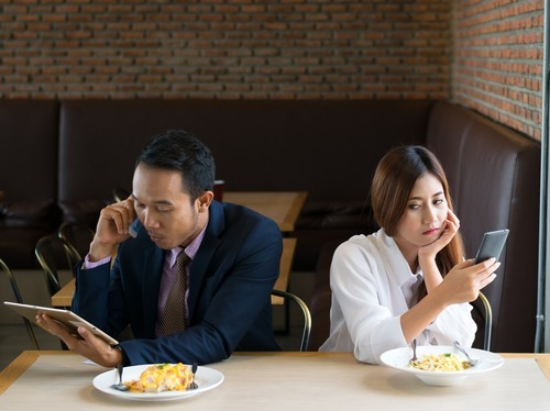 Asian couple in restaurant, looking away from each other and talking on their cell phones