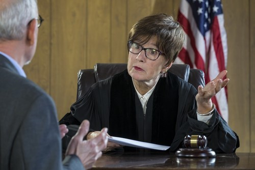 female judge behind bench listening to argument of older male lawyer