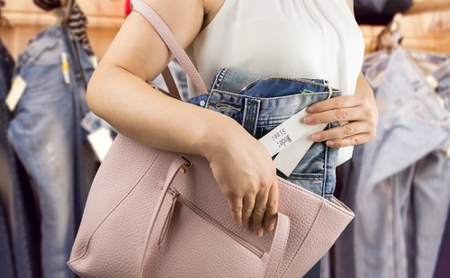woman putting new pair of jeans with tags into her purse