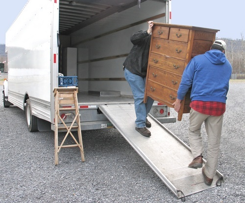 Two men carrying a chest of drawers into a moving van