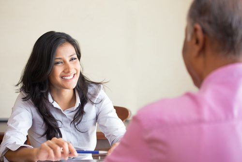 smiling female office manager interviewing an older male candidate