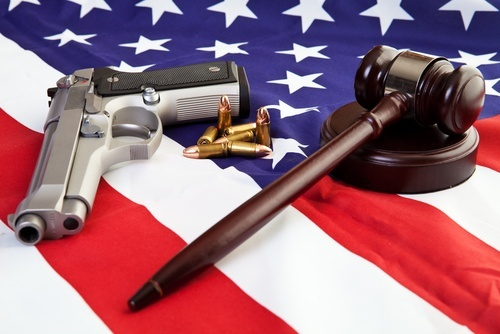 handgun and judge's gavel lying on an American flag