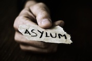 "hand holding out piece of paper with word ""asylum"" written on it"