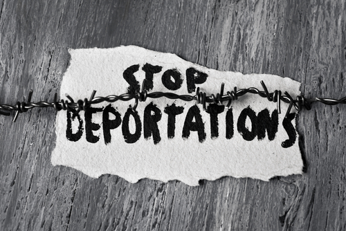 "Hand-painted sign reading ""stop deportations"" held onto piece of wood by barbed wire"