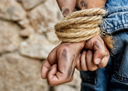 man's dirty hands bound with rope behind his back
