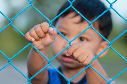 young Asian boy behind chain-link fence