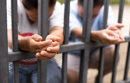 detained immigrants holding hands through bars seeking relief