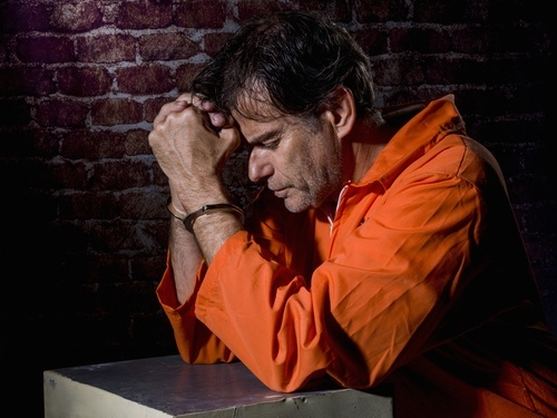 handcuffed prisoner in orange jumpsuit looking sorry for his actions