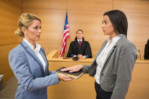 woman in blue suit swearing in young woman on bible as male judge looks on in courtroom