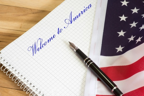 "pen lying on flag and notebook that reads ""Welcome to America"""